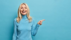 Positive senior woman laughs happily points away on blank space demonstrates shopping discount offer dressed in casual turtleneck isolated on blue background excited by good news or unexpected sale