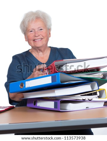Positive senior woman working part-time in the office to eek out her pension smiling cheerfully from behind a pile of files