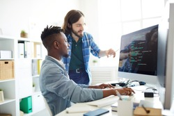 Positive skilled young multiethnic coders in casual clothing discussing computer language: smiling bearded man pointing at computer monitor while explaining web code to African colleague in office