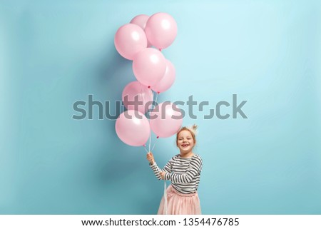 Positive small kid dressed in festive clothes, carries air balloons, celebrates holiday, has broad smile, stands against blue background, being in high spirit. Children and celebration concept #1354476785