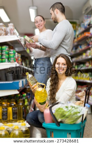 Positive smiling customers choosing seed-oil in plastic packing at shop. Focus on girl