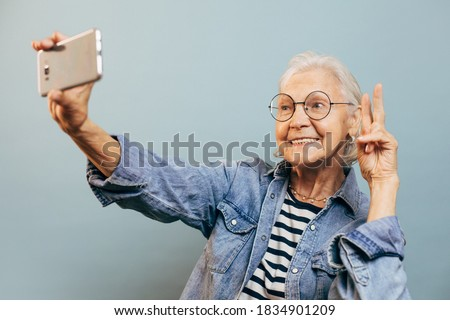 Positive smiling elderly woman wearing casual clothes and glasses poses for selfie holding smartphone in one hand and making peace or victory sign with another. Active old age concept