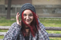 Positive smiling homeless red hair girl sitting on the bench on the street and looking in the camera  while she having fun, happy homeless concept