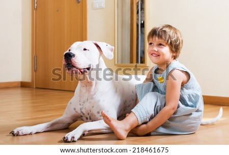 Positive smiling little girl with big white dog on the floor at home