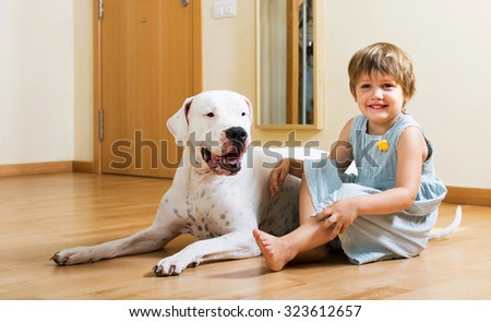 Positive smiling little girl with big white dog sitting on the floor at home