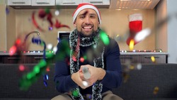 Positive smiling man in New Year red Santa Claus hat explodes confetti cannon. Male in blue sweater at home sits on couch on background kitchen with garland celebrates Christmas