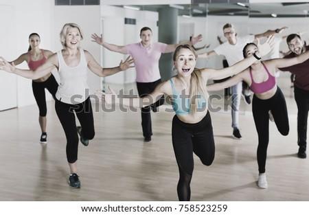 Positive smiling slim athletic women and men  dancing strip plastic in class #758523259