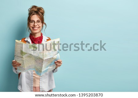 Positive smiling young female tourist searches for inspiring places, holds paper map, finds new sightseeing for discovering, wears round spectacles, red bandana, isolated on blue studio wall #1395203870