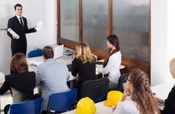 positive spanish architects having advanced training courses in classroom