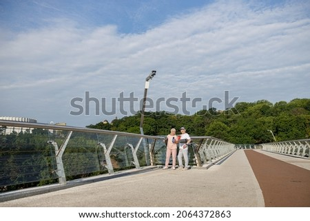 Positive sportive senior lady and man with rolled mats on footbridge