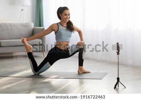Positive sporty lady stretching in front of smartphone at home, copy space. Beautiful young woman fitness blogger shooting video for her followers or having personal training online