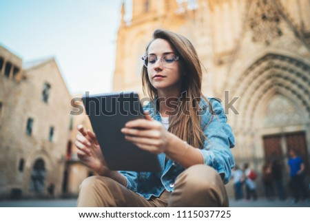 Positive student girl in trendy look sitting on steps using portable computer device for studying architecture or reading information about gothic historical buildings, young beautiful woman reading  #1115037725