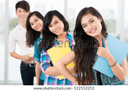 Positive students standing in a row and looking at camera