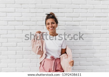 Positive tanned woman in white T-shirt puts on pink jacket. Portrait of lady with bun at background of white brick wall Stock fotó ©