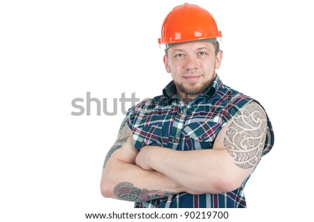 Positive tattooed manual worker in sleeveless work shirt and hardhat with his arms crossed, white background