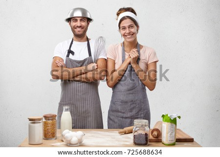 Positive team of young male and female cooks smile joyfully as recieve reward from chef, stand on kitchen at table, being glad to hear good comments about their work, get encouragement and praise