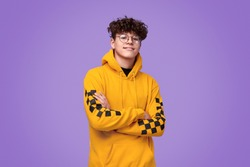 Positive teen boy in yellow hoodie crossing arms and looking at camera against bright violet background