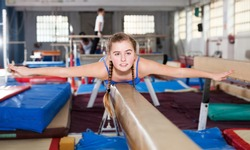 Positive teenage girl in gymnastic swimsuit training gymnastics at sport center