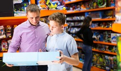 Positive teenager shopping together with father in store of kids toys, looking for new playthings