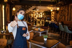 Positive thinking during the crisis caused by the coronavirus, young  woman waitress in uniform, wearing gloves and protective mask at work in the restaurant, makes the ok gesture with the hand