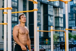 Positive topless muscular athlete under sports bar after pulling up on sportsground during workout.Naked torso man looking away, relaxing after exercises. Sport, lifestyle and people concept.