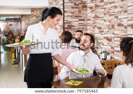 Positive waitress taking table order and smiling at the tavern  #797185465