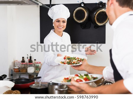 Positive woman cook in white uniform serving salad and giving it to waitress at restaurant's kitchen