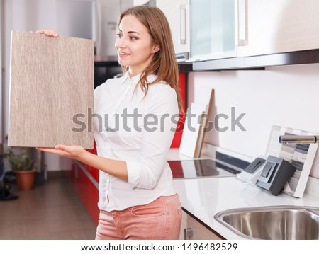 Positive woman looking for stylish materials for kitchen furnishing in store #1496482529