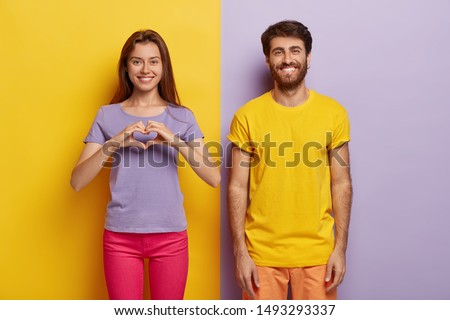 Positive woman makes heart gesture, expresses love and good feelings, her boyfriend stands near with toothy smile, wear bright clothes, being in good mood have romantic relationships bright background