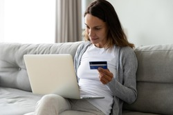 Positive woman paying online, using laptop, looking at screen, shopping in internet store, satisfied young female holding plastic credit card, making purchase, sitting on couch at home