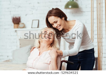 Positive woman taking care of her disabled grandmother