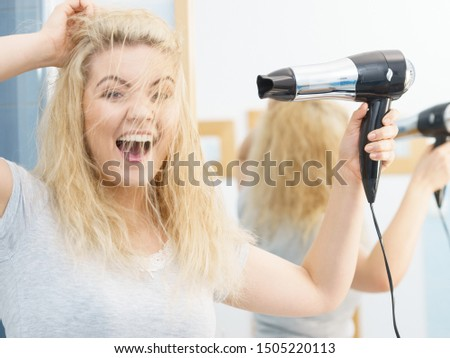Positive woman using hair dryer on her blonde hairdo. Haircare, hairstyling concept.