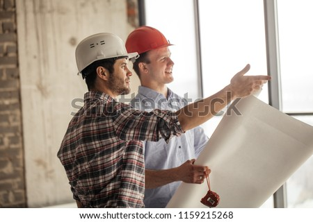 positive worker is showing the the progress of construction to a leader #1159215268