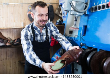 Positive worker repairing shoe in specialized workshop