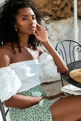 Positive young African American female with bowl in hands enjoying tasty healthy breakfast and smiling happily while sitting at table on sunny terrace in summer morning