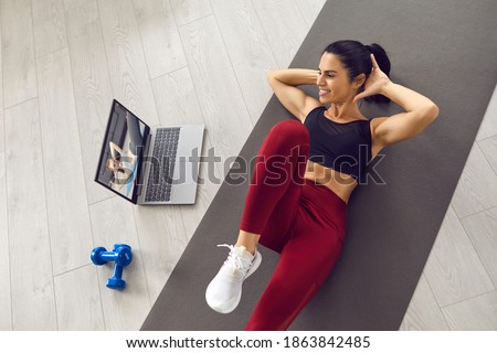 Positive young athlete exercising abs at home watching video workout lesson on laptop computer. Happy woman doing crunches following instructions of an online sports trainer. From above, high angle ストックフォト ©