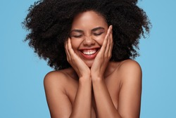 Positive young black female with bare shoulders and beautiful skin touching face and laughing with eyes closed on blue background
