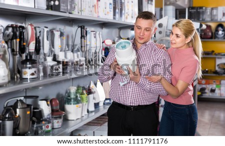 Positive young family couple is choosing blender for his kitchen in shop
