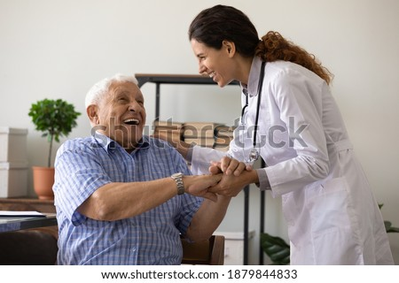 Positive young female nurse have fun laugh and joke with happy elderly male patient at consultation in hospital. Caring woman doctor support cheer and comfort mature man. Good medicine concept.