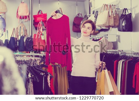 Positive young girl choosing colorful blouse in women's cloths shop
