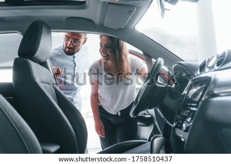 Positive young girl have a visit in autosalon and choosing car. Manager helping her.