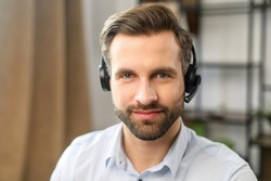 Positive young handsome bearded man employee in headset with microphone, working in the customer service department, looking at the camera, talking to customers on a helpline at the call center