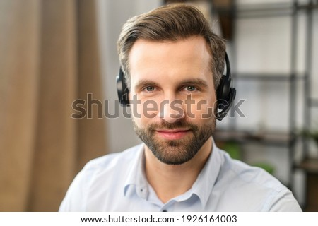 Positive young handsome bearded man employee in headset with microphone, working in the customer service department, looking at the camera, talking to customers on a helpline at the call center Stok fotoğraf ©