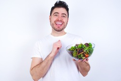 Positive Young handsome Caucasian man holding a salad bowl against white background smiles happily, glad to receive pleasant news from interlocutor, keeps hands together. People emotions concept.