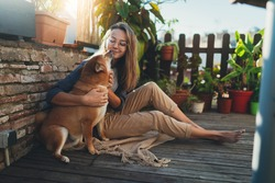 Positive young hipster girl having fun hugging with a dog sitting at home terrace with plants, Companionship Dog Best Friend, Sunny summer day outdoors with dog