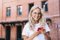 Positive young lady in stylish eyeglasses smiling at camera and browsing mobile phone while standing near modern building on city street