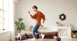 Positive young lady in wireless headphones and casual clothes listening to music with pleasure and dancing of sofa in light modern living room