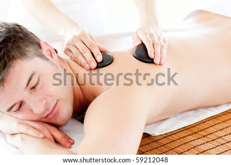 Positive young man enjoying a back massage with hot stone in a health spa