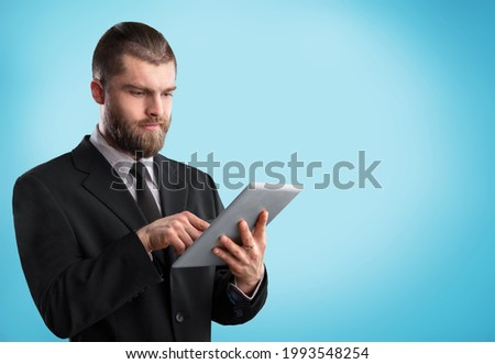 Positive young man using digital tablet for online work or studies.