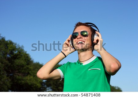 Positive young man wearing sunglasses and headphones